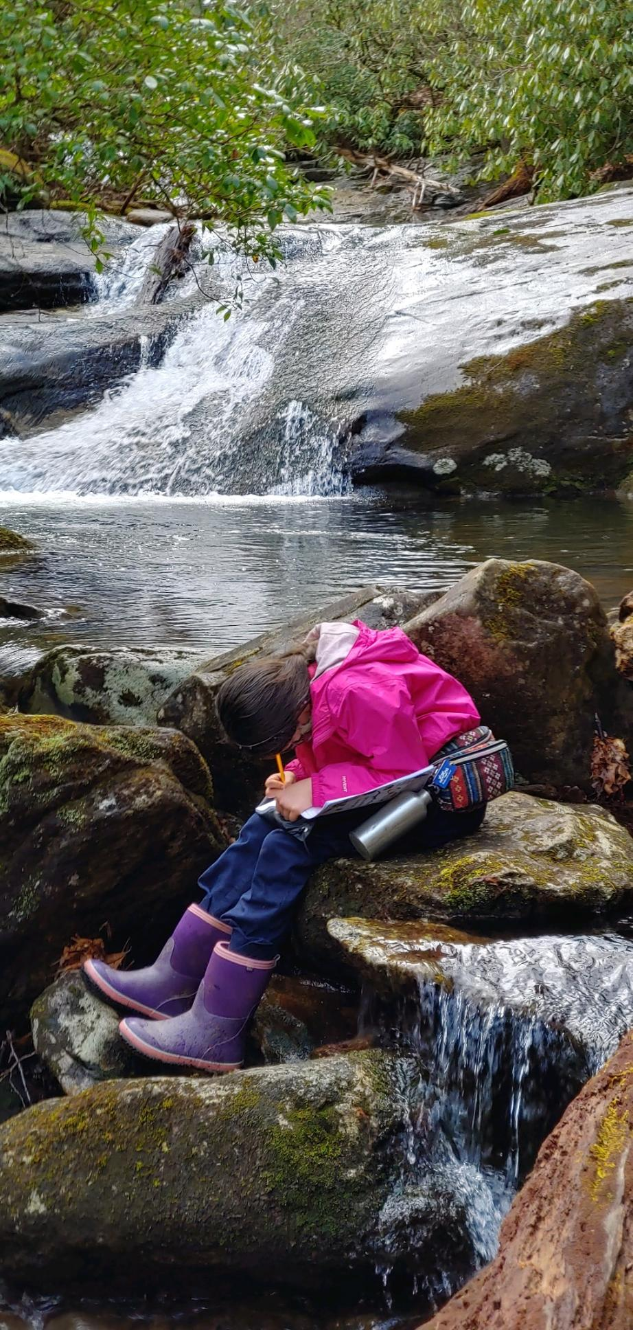 Child writing in front of waterfall