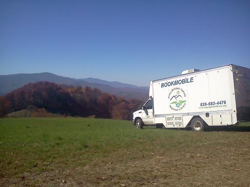 Image of the AMY Bookmobile on a green hill overlooking the mountains in the distance.